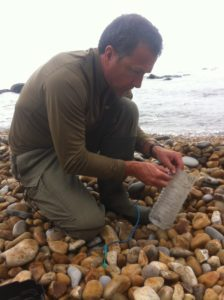 Survival fishing and hunting. Coastal survivor making traps from beach rubbish